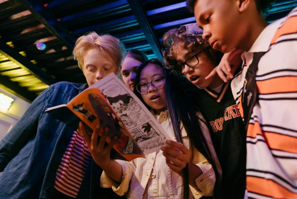Diverse group of kids looking at a comic book.