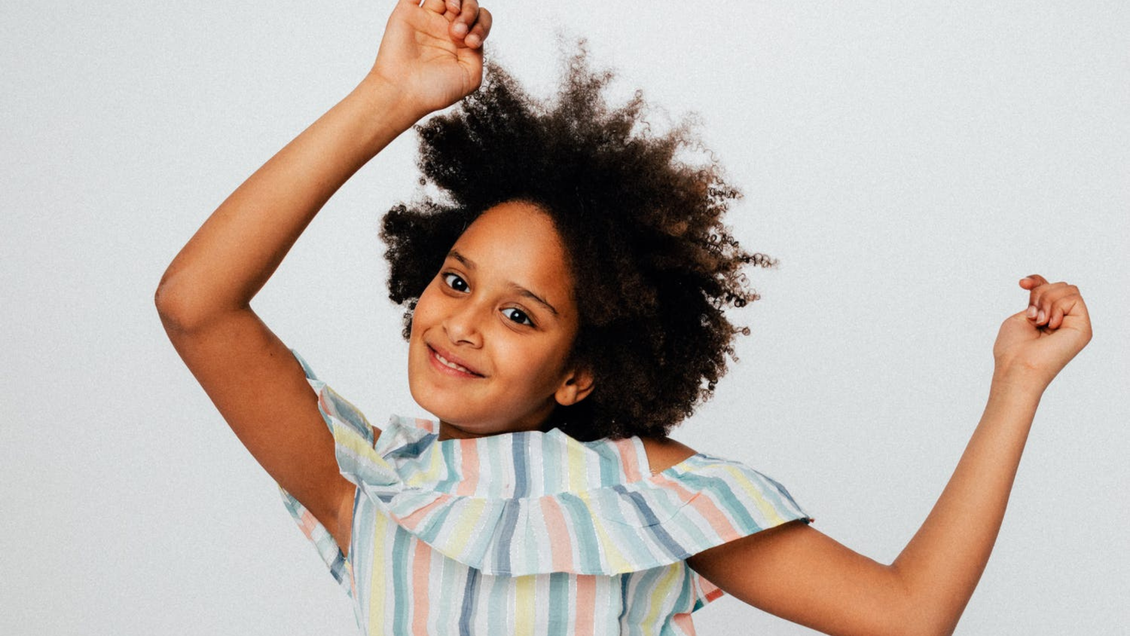 A young African American girl smiles at the camera wither her hands in the air